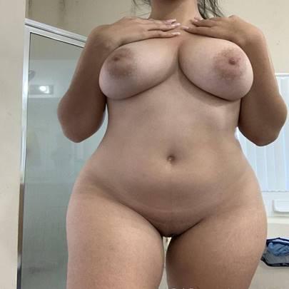Morena peituda tirando a roupa em fotos quentes